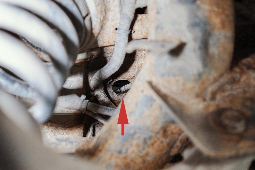 Место выхода троса находится рядом с левой задней пружиной