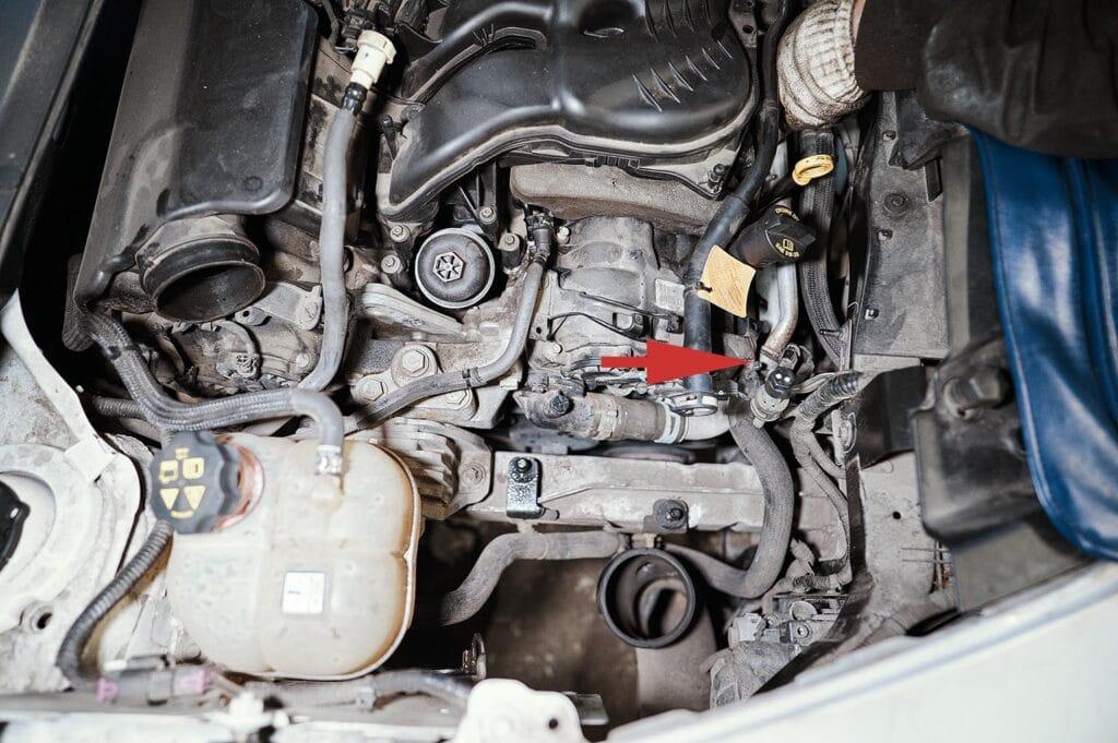 Трубка проходит между двигателем и радиатором